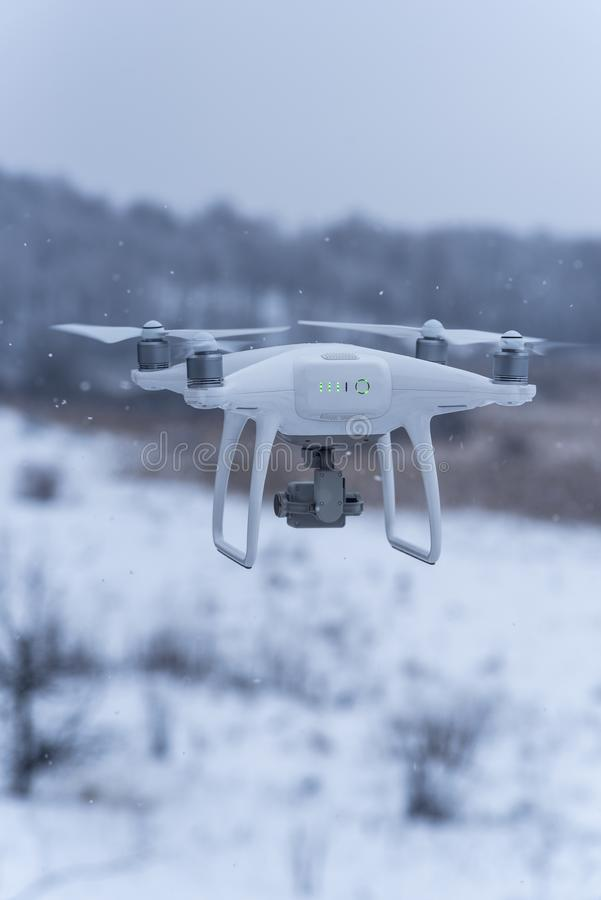 Hovering drone taking pictures of wild nature. Cold winter weather. Cloudy day with falling snow royalty free stock image