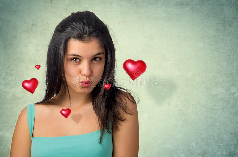 Hovering Hearts. Beautiful brunette teenager expressing a kiss with hovering hearts stock photography