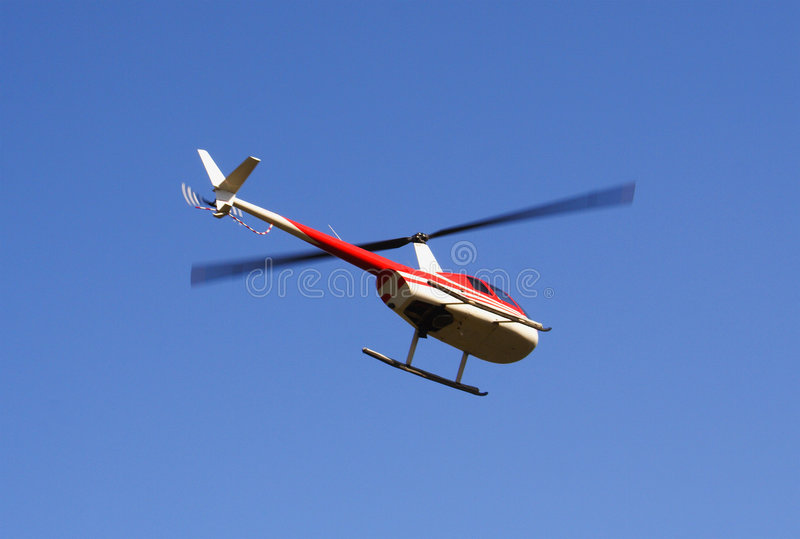 Hovering helicopter. A close up on a hovering helicopter in a blue sky stock photos