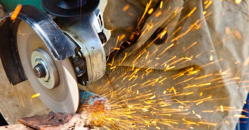 Hovslagare som grindering en metallplatta som rymmer en vinkelmolar skjuten från över Hovslagaren som grindering en metallplatta arkivbild