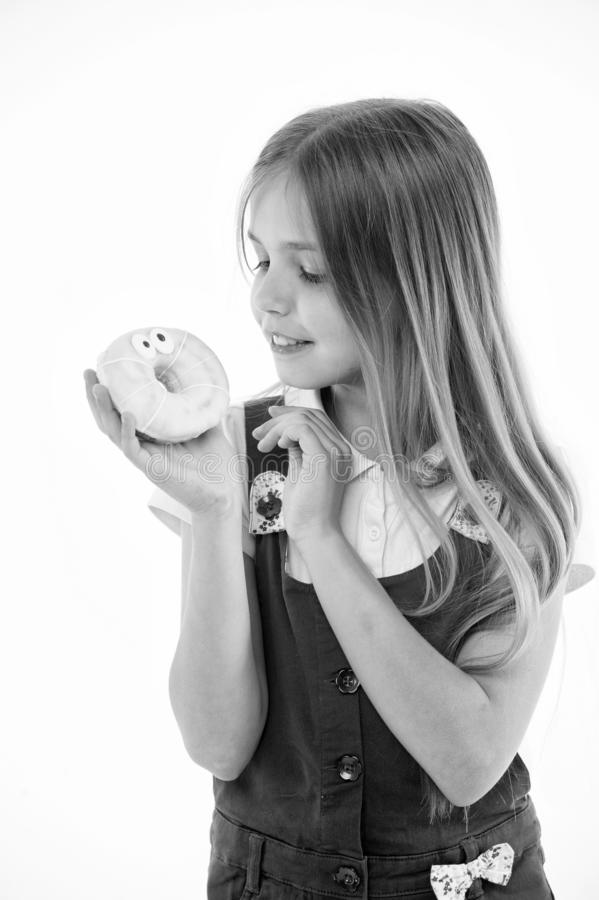 How bad are sweets for your kids. Girl cute smiling face holds sweet donut. Girl likes sweets as donuts. Avoid rewards. With sugar. Kid rewarded for good royalty free stock photo