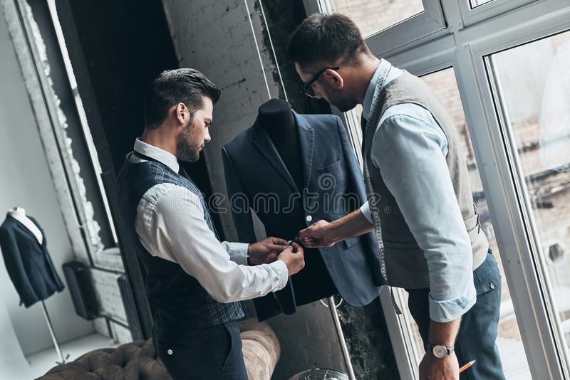 How do you like this one?. Two young fashionable men touching a jacket while standing in workshop stock photography