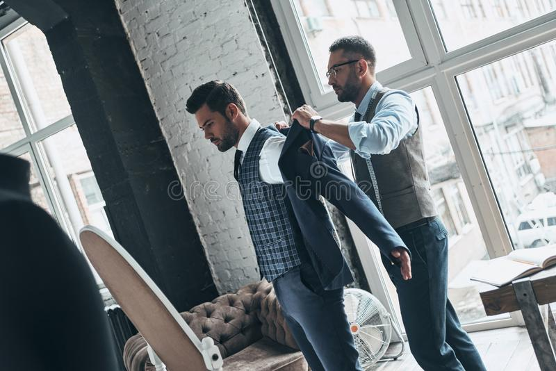 How do you like this?. Young fashionable designer helping his client to get dressed while standing in his workshop stock image