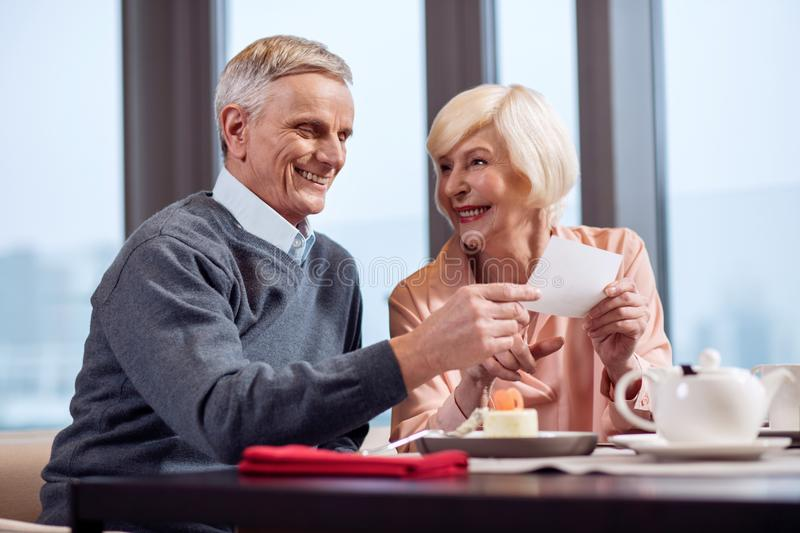 Cheerful mature couple reading card royalty free stock photography
