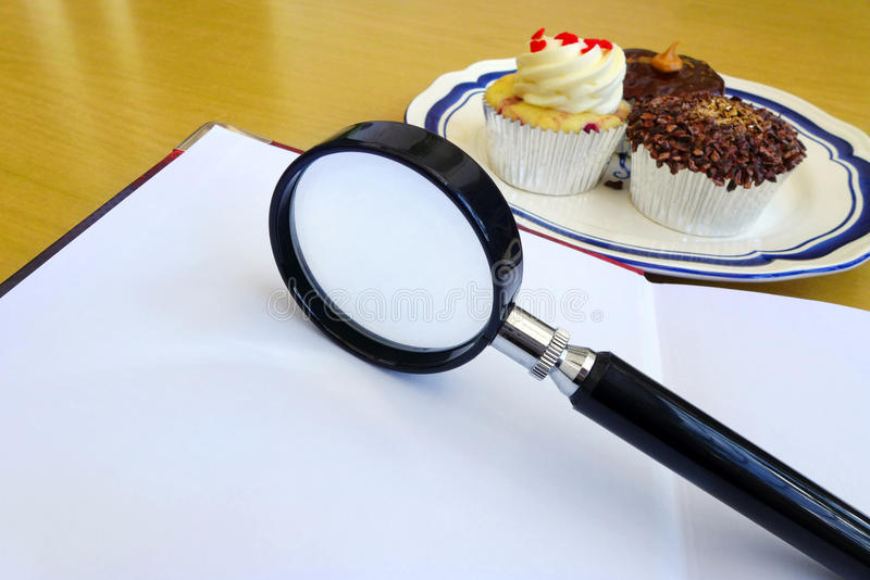 How many calories? Nutrition info concept. Count the calories! A photograph showing a plate of cream cup cakes coming under the analysis and scrutiny of a royalty free stock photography