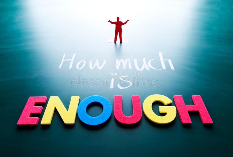 How much is enough concept. Man and words on blackboard stock photography