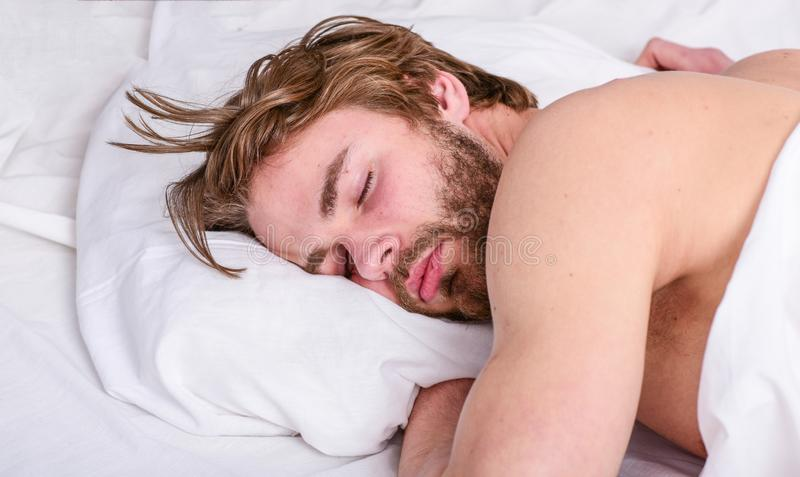 How much sleep you actually need. Man handsome guy lay in bed. Get adequate and consistent amount of sleep every night. Expert tips on sleeping better. Bearded stock image