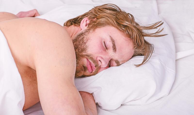 How much sleep you actually need. Man handsome guy lay in bed. Get adequate and consistent amount of sleep every night. Expert tips on sleeping better. Bearded royalty free stock image