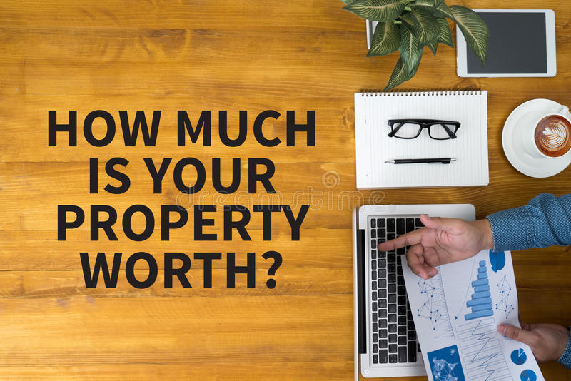 HOW MUCH IS YOUR PROPERTY WORTH?. Businessman working at office desk and using computer and objects, coffee, top view royalty free stock photos