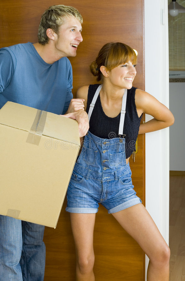 How nice!. Young couple getting in to new flat. They're looking happy and surprised. Man is holding box royalty free stock images