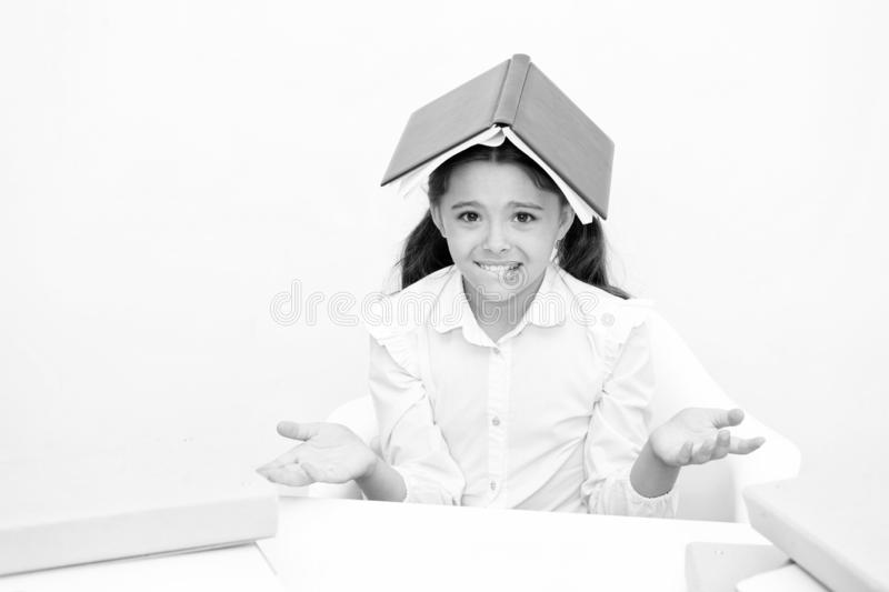 How is it possible to learn. Girl child confused exhausted with book roof on head white background. Schoolgirl tired of royalty free stock photos