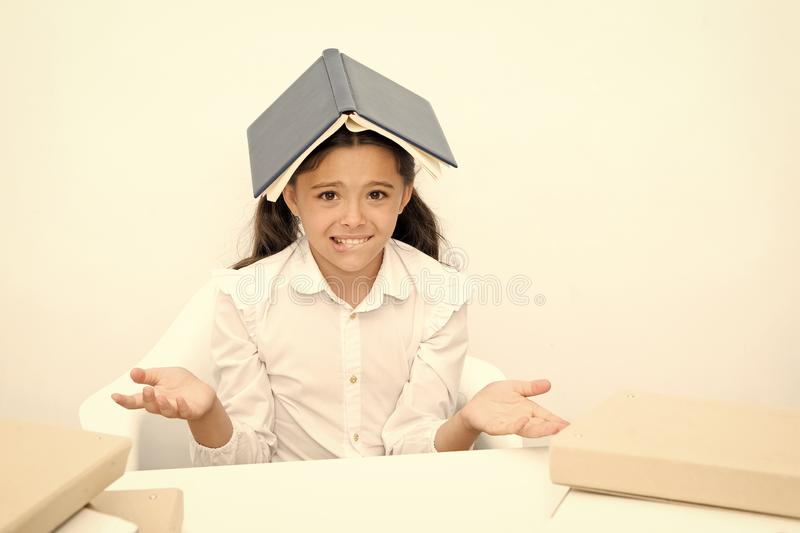 How is it possible to learn. Girl child confused exhausted with book roof on head white background. Schoolgirl tired of stock images