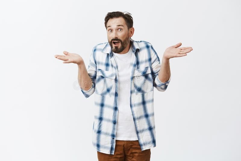 How should I know. Unaware confused adult guy with beard and moustache in casual checked shirt over t-shirt, shrugging. With raised spread palms and apologizing stock images
