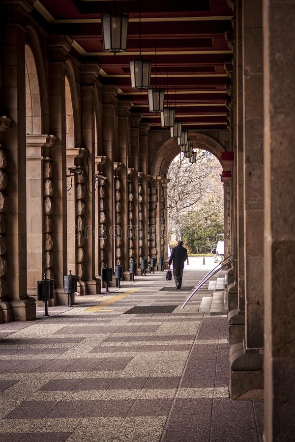 A man walks between the columns of a large old building. a tunnel formed by large columns. How small are the people to the big old royalty free stock photos
