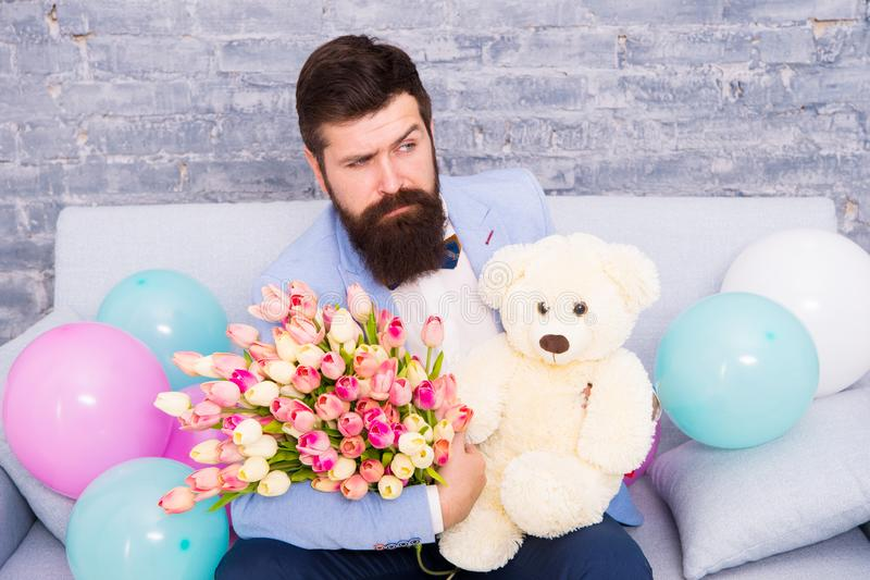 How successfully ask her dating. Romantic gift. Macho ready romantic date. Man wear blue tuxedo bow tie hold flowers. Bouquet. Romantic man with flowers and royalty free stock image