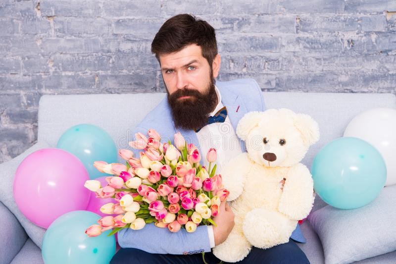 How successfully ask her dating. Romantic man with flowers and teddy bear sit on couch waiting girlfriend. Romantic gift. Macho ready romantic date. Man wear stock photography