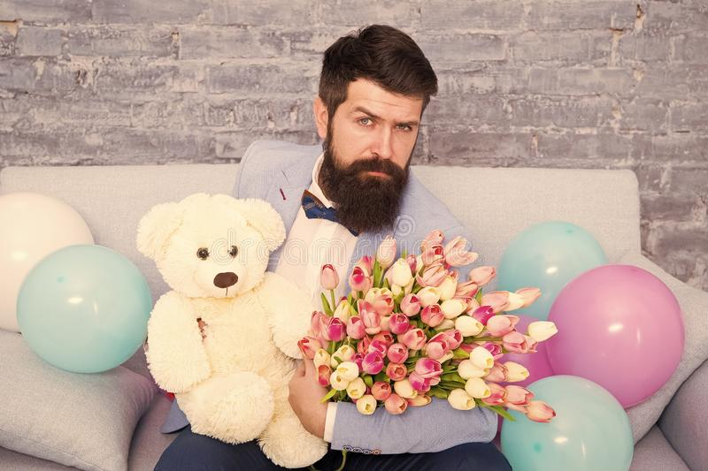 How successfully ask her dating. Romantic man with flowers and teddy bear sit on couch waiting girlfriend. Romantic gift royalty free stock images