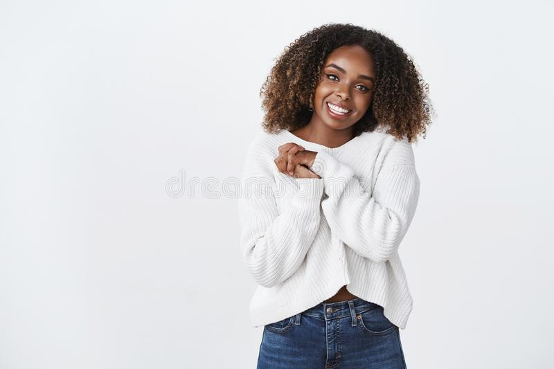 How sweet thanks. Charming delighted happy smiling african american curly haired woman wearing white sweater press palms royalty free stock images