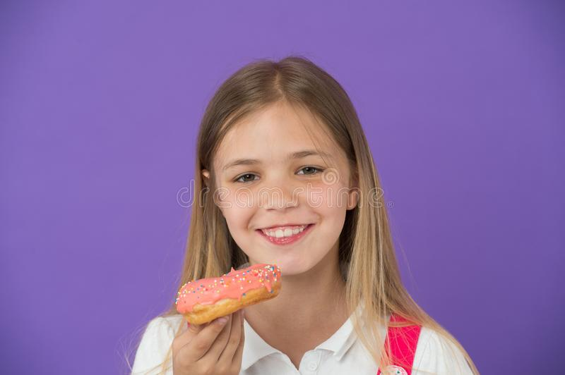 How tame childs sweet tooth. Kid rewarded for good behavior with sugary treats. Girl cute smiling face holds sweet donut royalty free stock photo