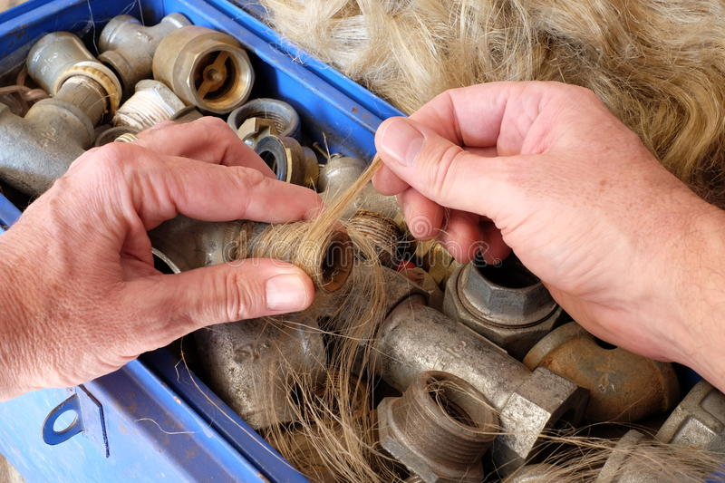 How to apply hemp on pipe thread. Showing how to apply hemp to the thread of a galvanized pipe stock photo