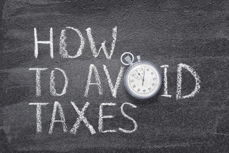 How to avoid taxes. Phrase written on chalkboard with vintage stopwatch used instead of O royalty free stock photography