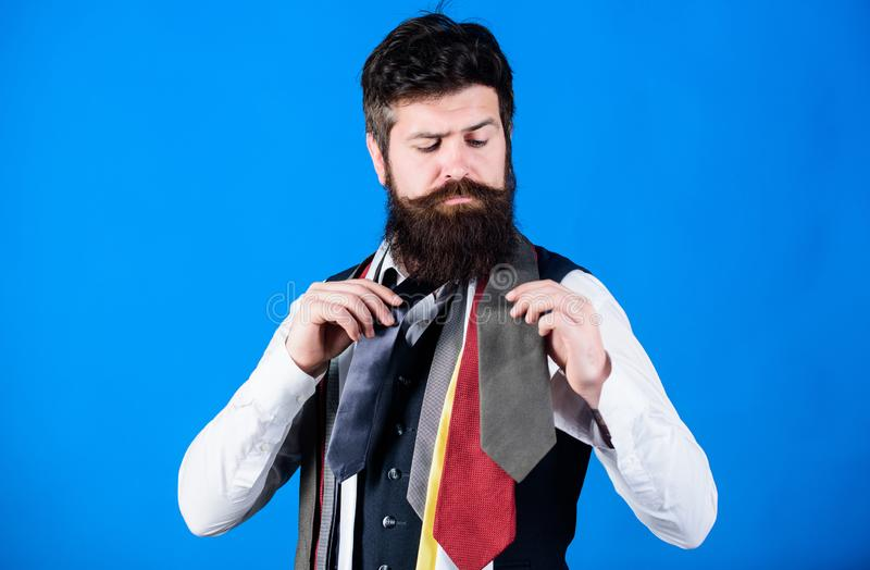 How to choose right tie. Classic style. How to match necktie with shirt and suit. Man bearded hipster hold few neckties stock images