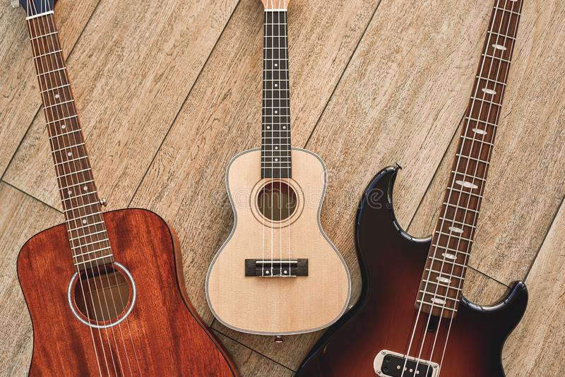 How To Choose Your First Guitar Top view on three different types of guitars: acoustic, electric and ukulele. royalty free stock photography