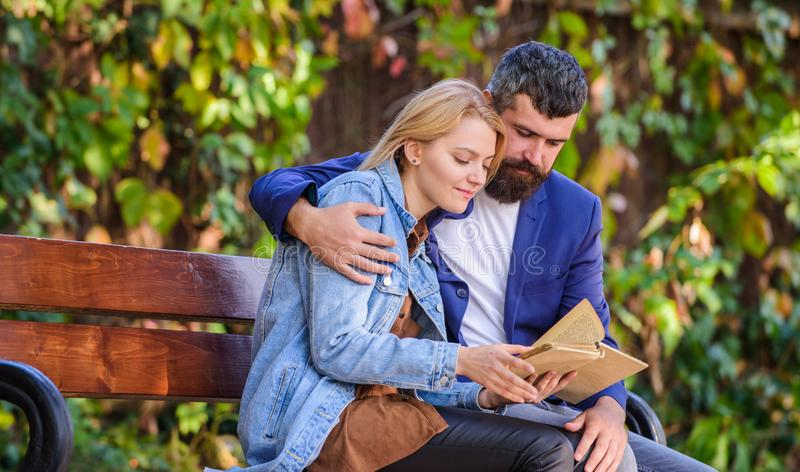 How to find girlfriend with common interest. Meeting people with similar interests. Man and woman sit bench park. Read stock photo