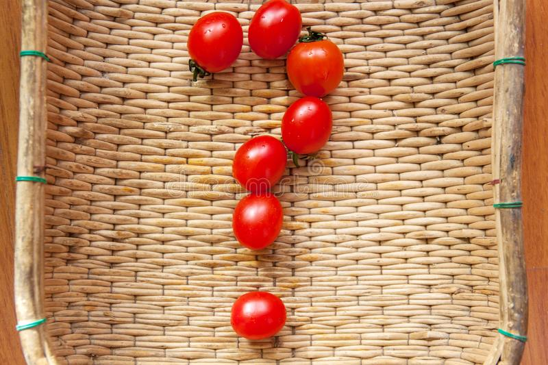 How to grow cherry tomatoes at home? What good is a tomato? How to choose a tomato? Small red cherry tomatoes spill out of a wicke stock photos