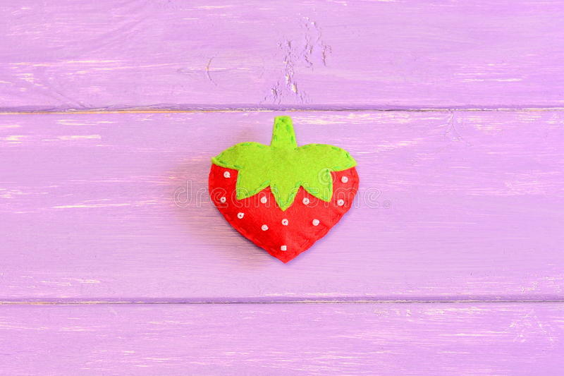 How to hand sew a children toy strawberry. Step. Tutorial. Kids felt toy strawberry on purple wooden background royalty free stock image