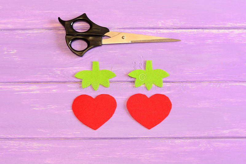 How to hand sew a children toy strawberry. Step. Tutorial. Parts cut from red and green felt in the shape of strawberries. Scissors on a wooden table. Easy royalty free stock images
