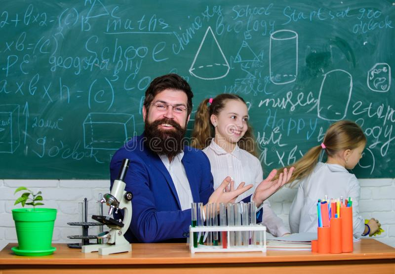 How to interest children study. Fascinating biology lesson. School teacher of biology. Man bearded teacher work with. Microscope and test tubes in biology stock image