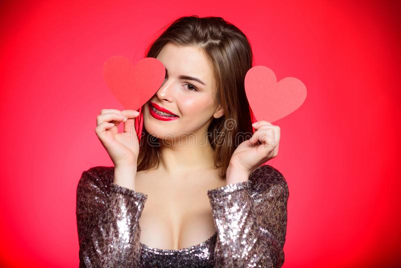 How to kiss with braces. Woman makeup red lips hold heart symbol love. Valentines day concept. Braces and beauty. Dating royalty free stock photos