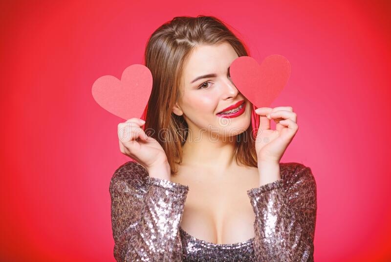 How to kiss with braces. Woman makeup red lips hold heart symbol love. Valentines day concept. Braces and beauty. Dating stock images
