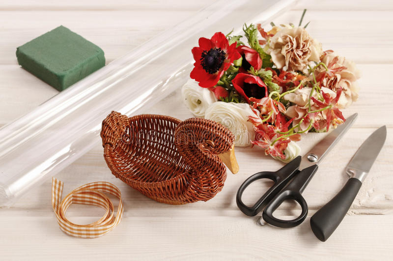 How to make bouquet of flowers in wicker goose. Table centerpiece idea for St. Martin's Day or St. Hubert's Day. Step by step, tutorial stock image