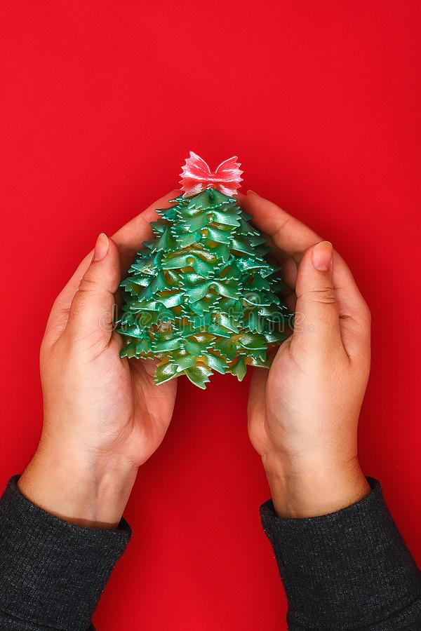 How to make a Christmas tree from raw pasta bows stock photo