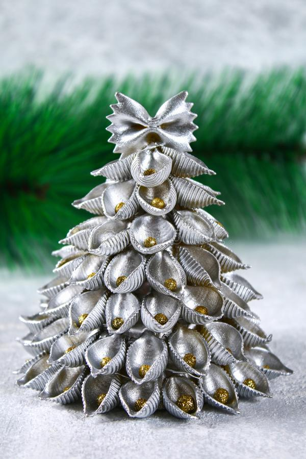 How to make a Christmas tree from raw pasta conchiglie. The process of making Christmas trees from pasta, cardboard plates, hot stock photos