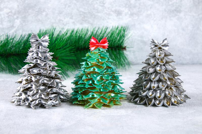 How to make a Christmas tree from raw pasta conchiglie. The process of making Christmas trees from pasta, cardboard plates, hot royalty free stock image