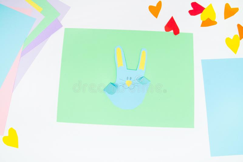 How to make paper bunny for Easter greetings and fun. Children art project. DIY concept. Kids hands makes paper craf. Step by step. Photo instruction. Step 12 stock photography