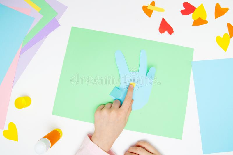 How to make paper bunny for Easter greetings and fun. Children art project. DIY concept. Kids hands makes paper craf. Step by step. Photo instruction. Step 10 royalty free stock image