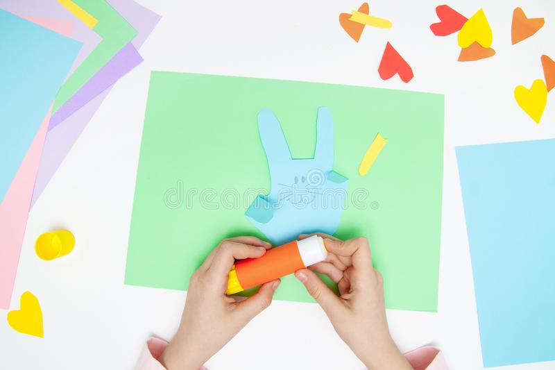 How to make paper bunny for Easter greetings and fun. Children art project. DIY concept. Kids hands makes paper craf. Step by step. Photo instruction. Step 9 royalty free stock images