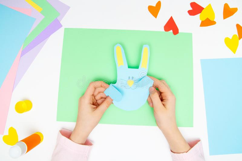 How to make paper bunny for Easter greetings and fun. Children art project. DIY concept. Kids hands makes paper craf. Step by step. Photo instruction. Step 11 stock image