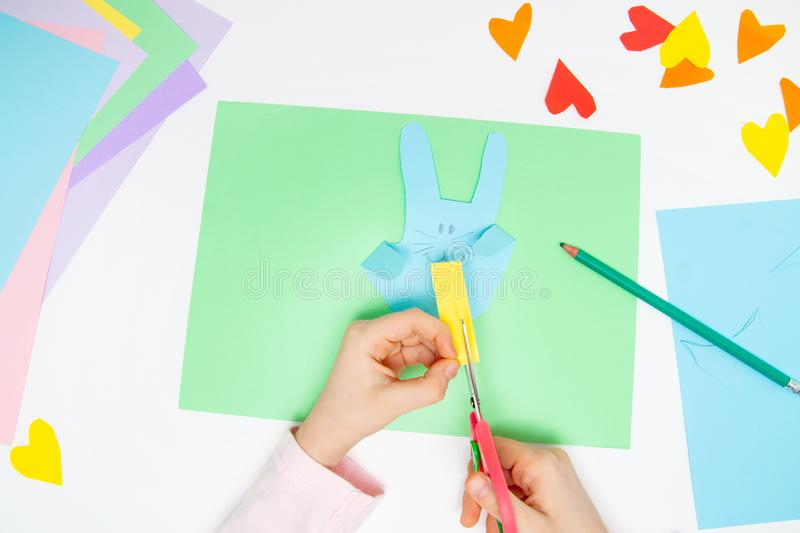 How to make paper bunny for Easter greetings and fun. Children art project. DIY concept. Kids hands makes paper craf. Step by step. Photo instruction. Step 8 royalty free stock images