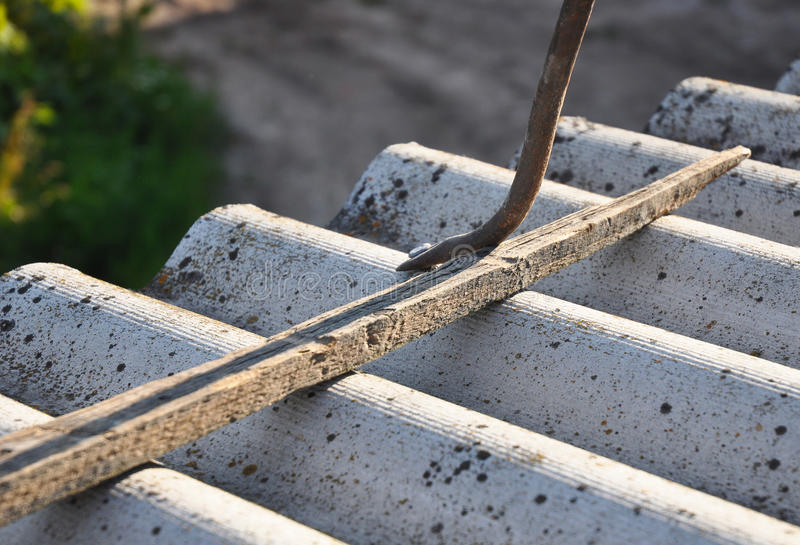 How to pull out the nails correctly from asbestos old roof tile. S. Roof worker repair dangerous asbestos old roof tiles. Roofing construction stock photo