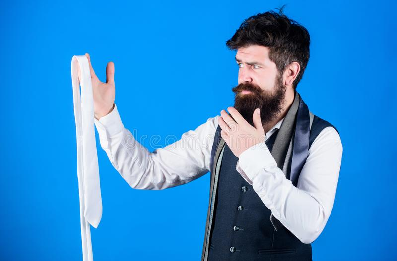 How to select tie. When dressing in suit necktie often add dash of flavor to overall outfit. Man bearded hipster hold. Few neckties. Guy with beard choosing stock image