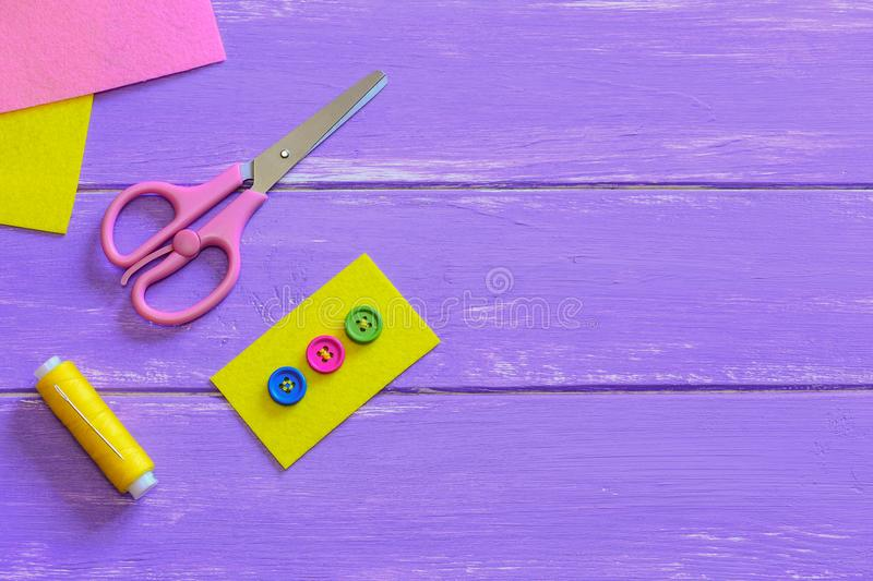 Colourful buttons on yellow felt piece. Scissors, thread, needle, felt pieces on a wooden background with copy space for text. How to sew a button by hand. Best stock images