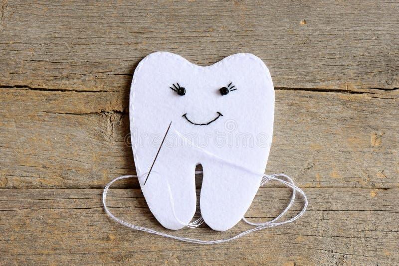 How to sew a felt tooth fairy. Step. Instruction for kids. Join the felt edges of felt tooth fairy with white thread. Vintage wood. Felt tooth fairy photo. Felt stock photography