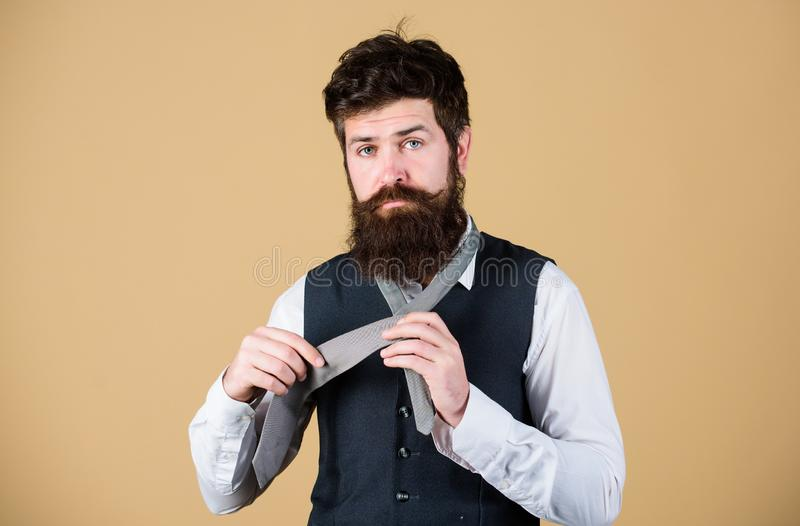 How to tie simple knot. Man bearded hipster try to make knot. Different ways of tying necktie knots. Art of manliness royalty free stock image