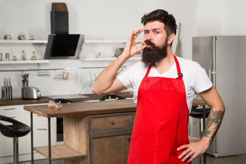 How to turn cooking at home into habit. Man bearded hipster red apron stand in kitchen. Kitchen furniture store. Cooking. In new kitchen. Weekend begins from stock photo