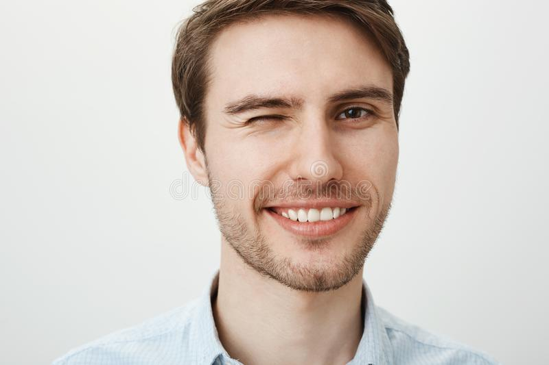 How you doing. Portrait of charming attractive caucasian guy winking and smiling sensually standing against gray. Background, flirting with woman from another stock images